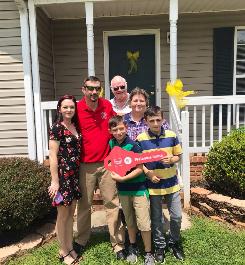Veteran and Family Standing in Front of House With Yellow Ribbons